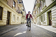 Germany, Hamburg, St. Pauli, Man riding bicycle in he city - RORF00827