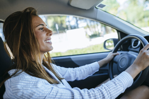 Smiling woman driving car - KIJF01445