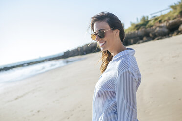 Smiling young woman wearing sunglasses on the beach - KIJF01454