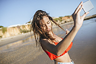 Young woman taking selfie on the beach with smartphone - KIJF01457