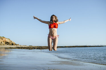 Smiling young woman jumping in the air on the beach - KIJF01460