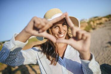 Portrait of smiling young woman making finger frame on the beach - KIJF01466