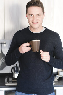Portrait of smiling man with cup of coffee in the kitchen - FMOF00254