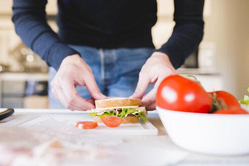 Man preparing sandwich in the kitchen, partial view - FMOF00260