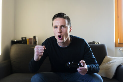Portrait of screaming man sitting on the couch with games console - FMOF00263