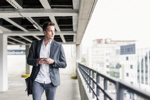 Young businessman using smartphone, walking on parking level - UUF10594
