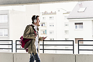 Young businessman using smartphone and headphones - UUF10597