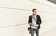 Young businessman walking in the street, carrying digital tablet and ear phones - UUF10603
