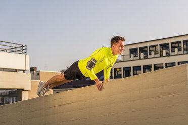 Young athlete exercising push ups on parking level - UUF10615