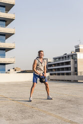 Young man exercising with kettle bell on a rooftop - UUF10624