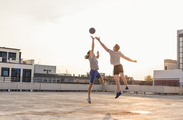 Friends playing basketball at sunset on a rooftop - UUF10636