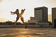 Friends jumping for joy at sunset - UUF10639