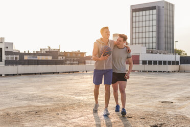 Friends playing basketball at sunset on a rooftop - UUF10642