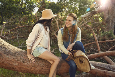 Two young women relaxing on tree trunk - SRYF00435