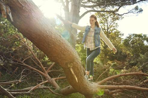 Young woman balancing on tree trunk - SRYF00438