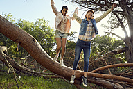 Two young women jumping hand in hand from tree trunk - SRYF00441