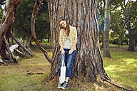 Smiling young woman leaning against tree trunk - SRYF00447