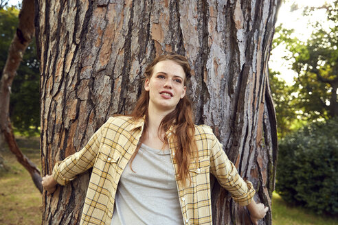 Portrait of young woman leaning against tree trunk - SRYF00450