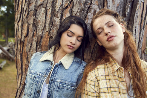 Portrait of two young women leaning against tree trunk with eyes closed - SRYF00453