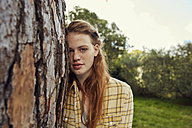 Portrait of young woman leaning against tree trunk - SRYF00456
