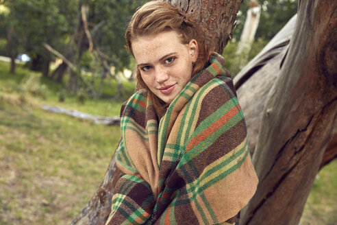 Portrait of young woman in nature wrapped in blanket - SRYF00462