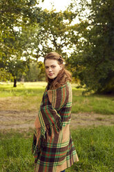 Portrait of young woman in nature wrapped in blanket - SRYF00465