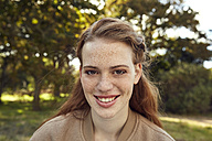 Portrait of smiling redheaded young woman with freckles - SRYF00471