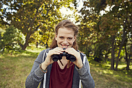 Portrait of smiling young woman using binoculars - SRYF00474