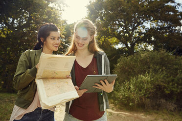 Two young women with tablet and map in nature - SRYF00480