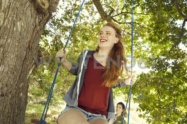 Portrait of smiling young woman sitting on a swing - SRYF00492