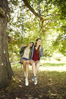 Two best friends sitting together on a swing - SRYF00495