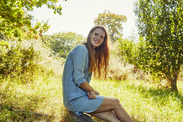 Portrait of smiling young woman sitting on a meadow - SRYF00504