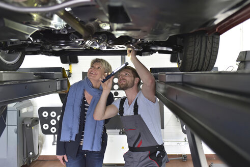 Car mechanic with client in workshop at car - LYF00690