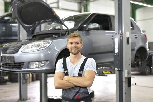Portrait of smiling car mechanic in a workshop - LYF00699