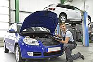 Car mechanic in a workshop using diagnostics computer at car - LYF00711