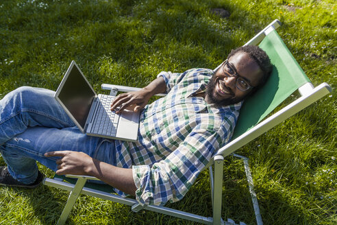 Smiling man with laptop sitting on deck chair on a meadow looking up to camera - TCF05410