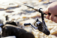 Hand holding fishing rod - KNTF00843