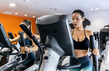 Two women working out in gym using an elliptical trainer - MGOF03268