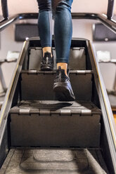 Close-up of woman training in gym with a stairs machine - MGOF03274