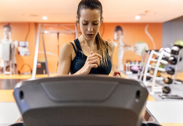 Young woman training in gym on a treadmil - MGOF03277