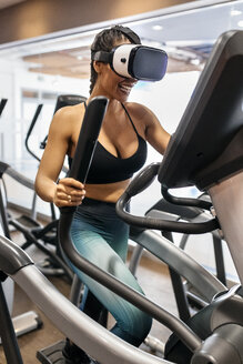 Woman wearing VR glasses on an elliptical traine in the gym - MGOF03295