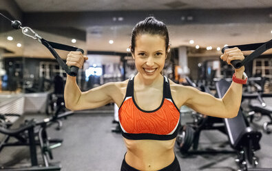 Portrait of a happy young woman working out in gym - MGOF03307