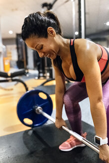 Woman lifting barbell in gym - MGOF03313