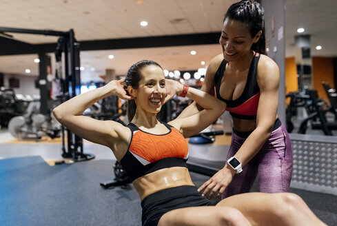 Woman with her trainer working out in gym - MGOF03325