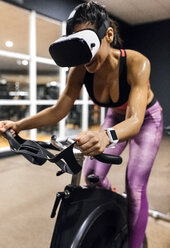 Woman with VR glasses on spinning bike in the gym - MGOF03328