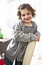 Portrait of smiling little girl kneeling on a chair at home - FSF00833