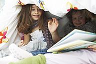 Three little children with book together under blanket - FSF00845