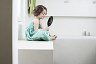 Smiling little girl watching herself in hand mirror in the bathroom - FSF00848