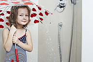 Portrait of smiling little girl taking shower with umbrella - FSF00851