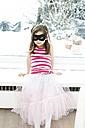 Portrait of little girl wearing mask sitting on window sill - FSF00857